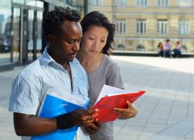 Man and woman with folders of information, urban campus buildings in backgroun